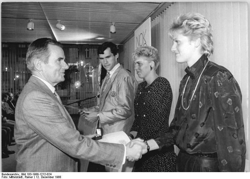 Der Präsident des Nationalen Olympischen Komitees der DDR, Manfred Ewald, gratuliert am 12. Dezember 1988 den Olympiasiegern Kristin Otto (SC DHfK Leipzig, r.), Kathleen Nord (SC Magdeburg, 2.v.r.) und Bernd Nissecke (SG Dynamo Potsdam, 3.v.r.). Der Sportfunktionär, der zwischen 1961 und 1988 als Präsident des DTSB amtiert, ist an der Einrichtung und Durchsetzung des flächendeckenden Dopingsystems in der DDR entscheidend beteiligt.
