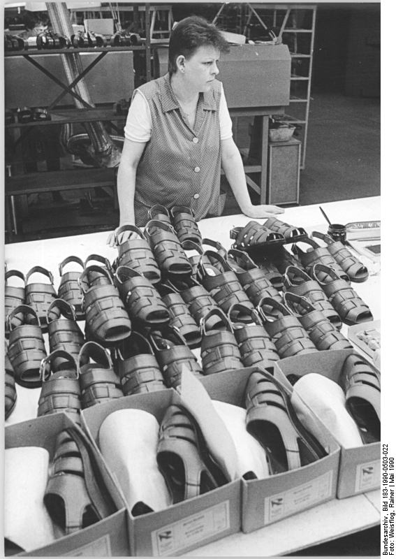 Arbeiterin aus der Schuhfabrik Lauchhammer im Mai 1990. Obwohl die Fabrik erst 1989 eröffnet wurde können die dort gefertigten Schuhe aufgrund der hohen Produktionskosten nicht mehr verkauft werden. Quelle: Bundesarchiv, Bild 183-1990-0503-022, Fotograf: Rainer Weisflog