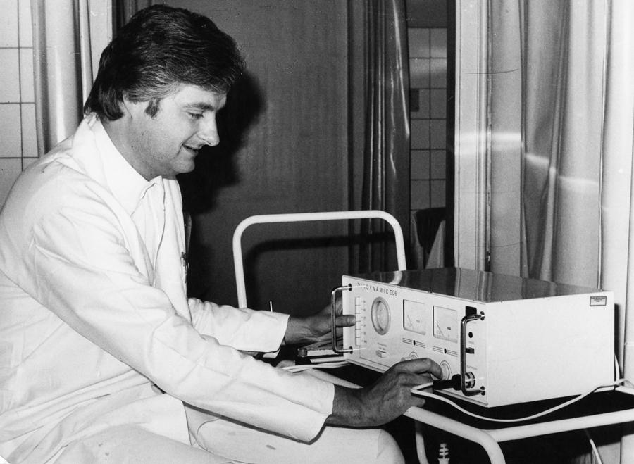 """Medizinischen Akademie """"Carl Gustav Carus"""" Dresden, Klinik für Orthopädie, Abt. Physiotherapie, ca. 1977. Orthopäde Dr. Jürgen Kleditzsch testet ein neues Elektrotherapiegerät. Quelle: Privatarchiv Jürgen Kleditzsch"""