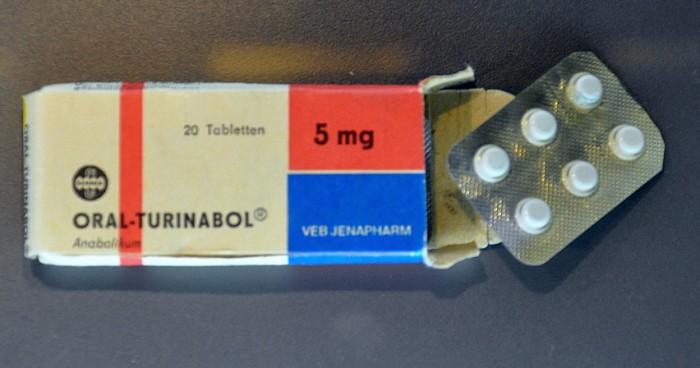 """Das Medikament """"Oral-Turinabol"""" wird im DDR-Doping vor allem Mädchen und Frauen verabreicht. Es enthält ein männliches Sexualhormon, das zu schnellem Muskelwachstum und Leistungssteigerungen führt. Die Einnahme über einen längeren Zeitraum oder Überdosierungen führen bei zahlreichen DDR-Sportlerinnen zu schweren Nebenwirkungen und Gesundheitsschädigungen."""
