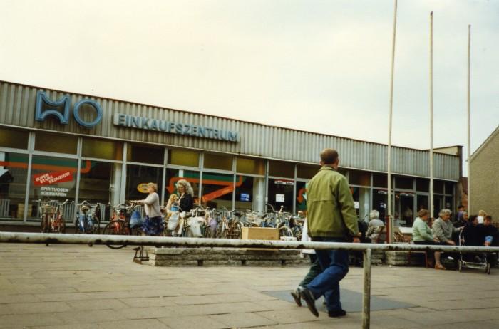 Ansicht eines Einkaufszentrum der HO am 1. Juli 1990 in Brandenburg. An den Schaufenstern ist bereits westliche Produktwerbung angebracht.