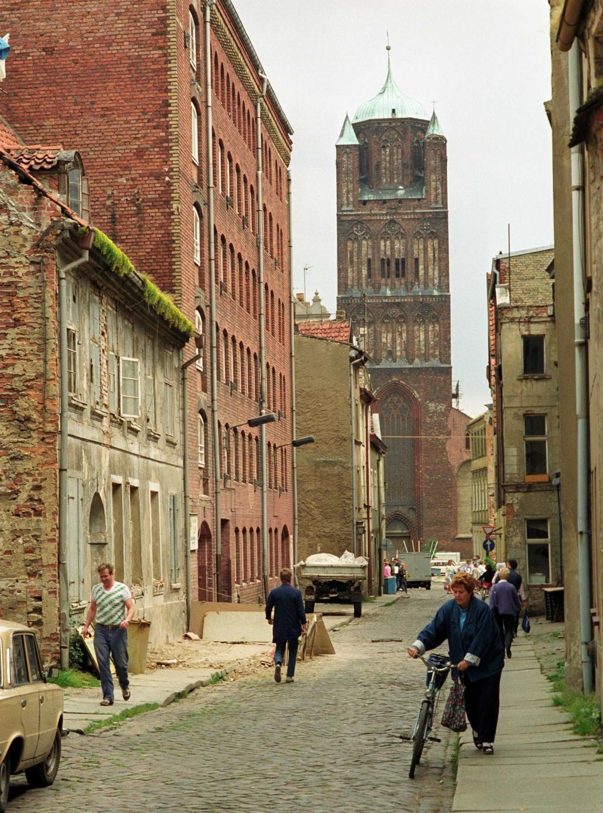 Böttcherstraße mit Blick auf St. Jakobi, dreischiffige Backsteinbasilika aus dem 14. und 15. Jahrhundert in Stralsund, Juni 1990.