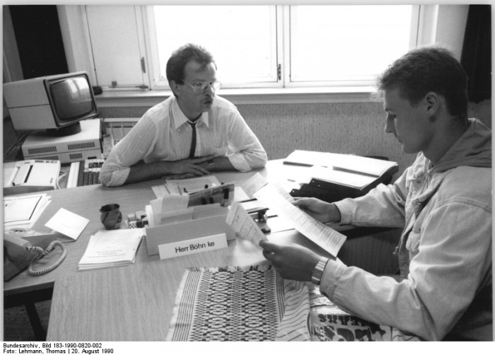 Berlin, Arbeitsamt, Sachbearbeiter berät Arbeitslosen. Quelle: Bundesarchiv, Bild 183-1990-0820-002, Fotograf: Thomas Lehmann