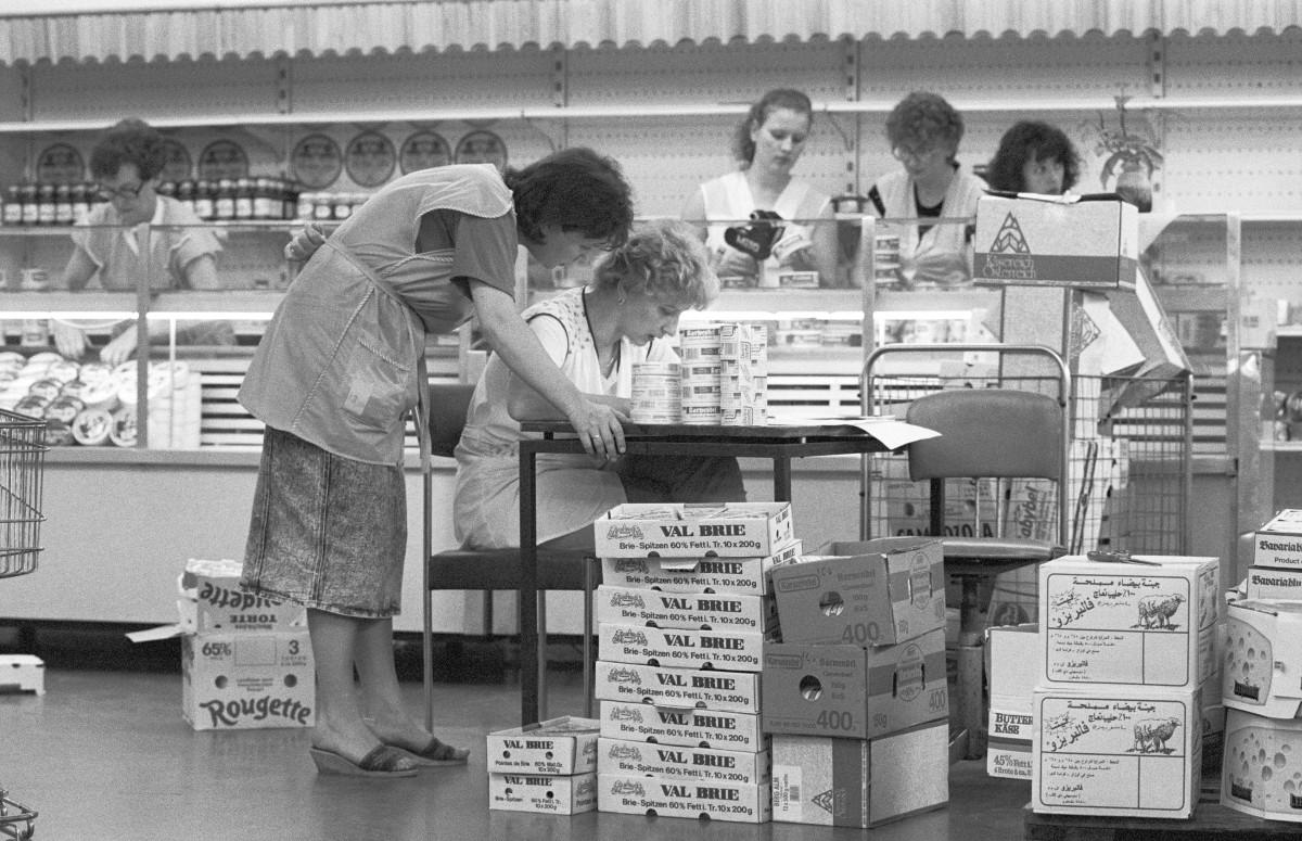 Verkäuferinnen einer Konsumfiliale bei Frankfurt Oder ettiketieren neu aus dem Westen angelieferten Waren, 1. Juli 1990