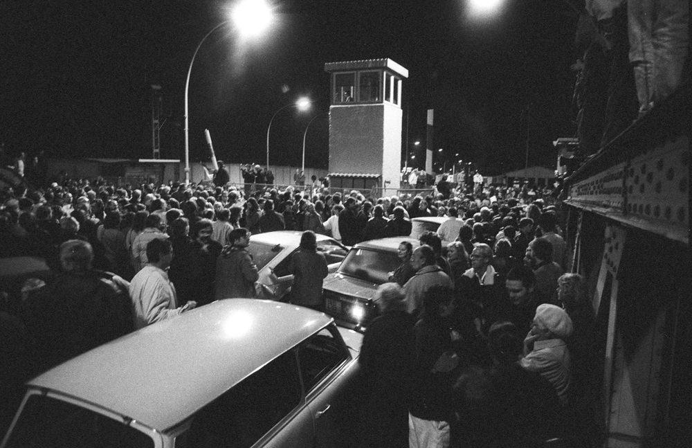 9. November 1989: Nach der Bekanntgabe der neuen Reiseregelungen in Funk und Fernsehen machen sich tausende Ost-Berlinerinnen und -Berliner in den Abendstunden auf den Weg zu den Grenzübergangsstellen. Die Grenztruppen haben keine Anweisungen und sind mit der Situation völlig überfordert. Schließlich geben sie dem Druck nach und öffnen die Grenze. Hier: GüSt Bornholmer Straße