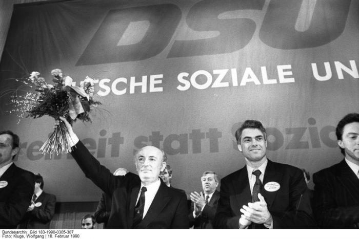 Pfarrer Hans-Wilhelm Ebeling (l.) auf dem DSU-Parteitag am 18. Februar 1990, dessen Vorsitzender er zu diesem Zeitpunkt ist. Quelle: Bundesarchiv, Bild 183-1990-0305-307, Fotograf: Wolfgang Kluge