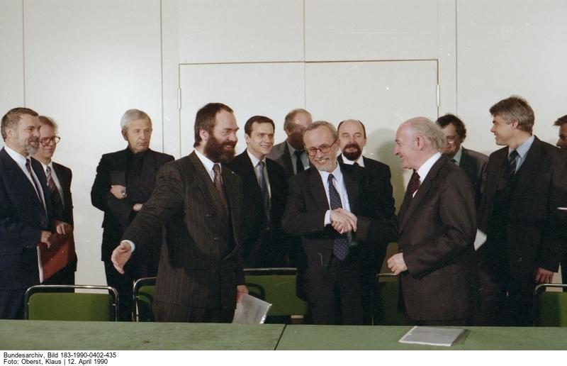 Unterzeichnung der Koalitionsvereinbarung am 12. April 1990. Vorn v.l.n.r.: Markus Meckel (SPD), Lothar de Maizière (CDU) und Hans-Wilhelm Ebeling (DSU). Quelle: Bundesarchiv, Bild 183-1990-0402-435, Fotograf: Klaus Oberst